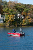 Two fishermen fishing from a boat in Lake Delavan, Wisconsin. Two fishermen are standing in a small red boat fishing in the middle of the blue water of Lake Stock Images