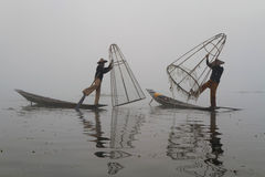 Two fishermen in the fog Stock Images