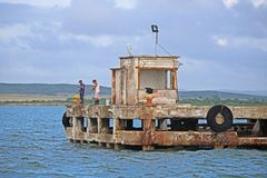 Fisherman At The End Of Antilla Wharf In Cuba. Two fishermen look for fish at the end of the crumbling wharf in Antilla, Cuba. Once a rail / shipping port, the royalty free stock photography