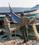 Two fishermen near boats in a small village of Portugal in the 80s royalty free stock photo