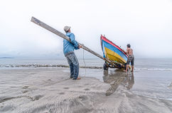 Two fishermen pull the boat. In the morning Royalty Free Stock Photos