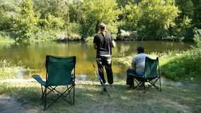 Two fishermen on the riverbank. Two fishermen sit on chairs on a river and communicate stock footage