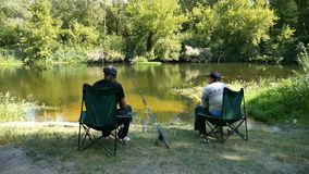 Two fishermen on the riverbank. Two fishermen sit on chairs on a river and communicate stock video footage