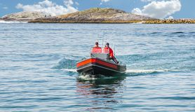 Two fishermen sail on a motor boat. Float directly to the camera royalty free stock photos