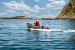 Two fishermen sail on a motor boat. Move to the left royalty free stock image