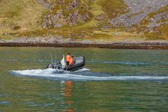 Two fishermen sail on a motor boat. stock photos