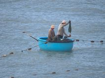 Two fishermen sail in a traditional Vietnamese boat. One of them throws the net royalty free stock images