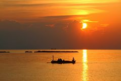 Beautiful sunset with silhouette of a small fishing boat stock images