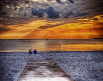 Two fishermen on the sand at sunset in hdr Stock Photography