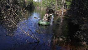 Two fishermen set in the taiga river fishing net. Two fishermen on an inflatable boat set in the taiga river fishing net stock video