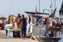 Two Fishermen standing near their fishing trawler. Trieste, Italy stock photo