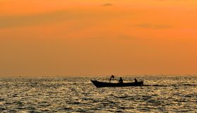 Two fishermen Take a small fishing boat to the sea at sunset Stock Photo