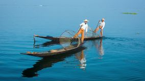 Two fishermen on traditional boats turning. Inle Lake, Myanmar stock video