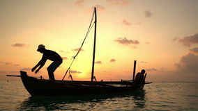 Two fishermen wash old boat at sunset in the Indian Ocean. Two fishermen scooped water out of an old wooden boat at the end of a hard day at sunset in the stock footage