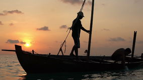 Two fishermen wash old boat at sunset in the Indian Ocean. Slow motion. Two fishermen scooped water out of an old wooden boat at the end of a hard day at sunset stock video footage
