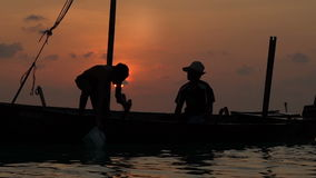 Two fishermen wash old boat at sunset in the Indian Ocean. Slow motion. Two fishermen scooped water out of an old wooden boat at the end of a hard day at sunset stock video