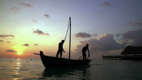 Two fishermen wash old boat at sunset in the Indian Ocean. Slow motion. Two fishermen scooped water out of an old wooden boat at the end of a hard day at sunset stock footage