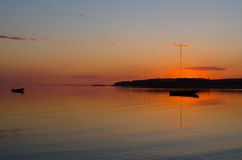 Two fishing boats in bay during a colorful orange sunset Stock Images