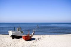 Two fishing boats on beach. Two fishing boats standing on the sand of a beach. Clear sky and horizon, nobody in the photo. The Baltic Sea Royalty Free Stock Photography