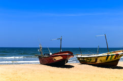 Two fishing boats on the beach by ocean Royalty Free Stock Photography