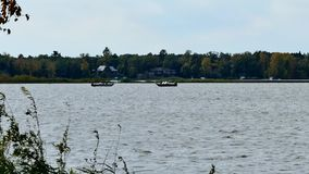 Two fishing boats on a lake in early autumn.