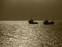 Two Fishing Boats. Moored off Holy Island in Northumberland, England. They have been silhouetted against the sunlight Royalty Free Stock Photos