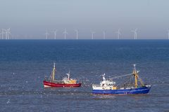 Two fishing boats with seagulls on the north sea stock image