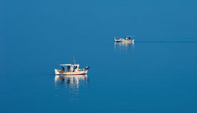 Two fishing boats in serene scene Royalty Free Stock Images
