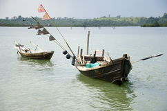 Two fishing boats sitting on the rivers edge Royalty Free Stock Photography