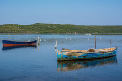 Two fishing boats in the water. Two lonely fishing boats in the calm water, reflections visible in the water. Clear blue sky and horizon, nobody in the photo Royalty Free Stock Images