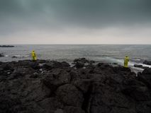 Two fishing mans in yellow jackets. Two fishing mans in yellow jackets on the ocean of Jeju Island, South Korea stock photography