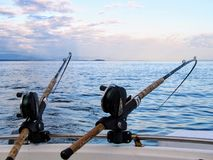 Two fishing rods held in fishing rod holders, attached to a back of a boat. The rods are bent from the weight of the down riggers stock photography