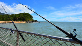 Two fishing rods on Palm Cove pier Queensland  Australia Stock Photo