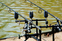 Two fishing rods in a rod holder. Two fishing rods with attached lines and reels in a rod holder overlooking the calm water of a freshwater lake in a close up Royalty Free Stock Images