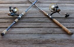 Rods. Two fishing rods on wooden background Royalty Free Stock Photo