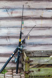 Two fishing rods and wooden box standing outside. Spinning equipment concept. Two fishing rods and old rotten wooden box standing outside in front of wooden wall royalty free stock image