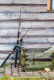 Two fishing rods and wooden box standing outside. Spinning equipment concept. Two fishing rods and old rotten wooden box standing outside in front of wooden wall stock images