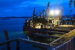 Old Fishing Boats in Harbor at Nighttime stock photo