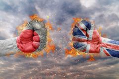 Two fist with the flag of Japan and Great British faced at each other. Ready for fight Royalty Free Stock Photos