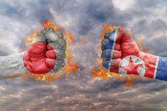 Two fist with the flag of Japan and North Korea faced at each other. Ready for fight Stock Image