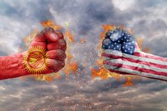 Two fist with the flag of Kyrgyzstan and USA faced at each other Stock Images