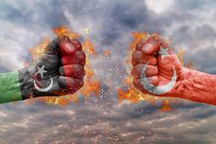 Two fist with the flag of Libya and Turkey faced at each other. Ready for fight stock photo