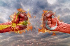Two fist with the flag of Macedonia and Turkey faced at each other. Ready for fight stock photos