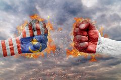 Two fist with the flag of Malaysia and Indonesia faced at each other. Ready for fight stock image
