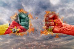 Two fist with the flag of Mozambique and China faced at each other. Ready for fight Stock Photography