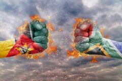 Two fist with the flag of Mozambique and South Africa faced at each other. Ready for fight Royalty Free Stock Image