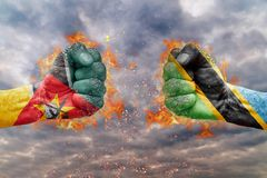 Two fist with the flag of Mozambique and Tanzania faced at each other. Ready for fight Stock Photography
