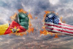 Two fist with the flag of Mozambique and USA faced at each other. Ready for fight Royalty Free Stock Image