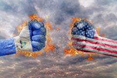 Two fist with the flag of Nicaragua and USA faced at each other. Ready for fight Stock Image