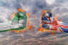 Two fist with the flag of Nigeria and Great Britain faced at each other. Ready for fight Royalty Free Stock Images